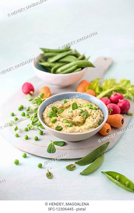 Houmous made of chickpeas, peas with mint and tahini, fresh vrgetables foe dipping on a side