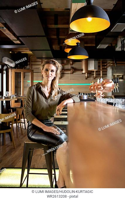 Woman with blond hair sitting at bar counter in coffee shop