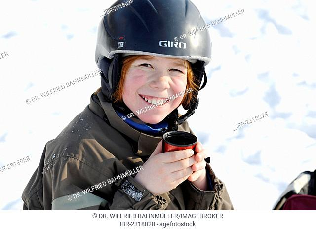 Boy drinking a cup of tea during wintersports in the snow, Germany, Europe