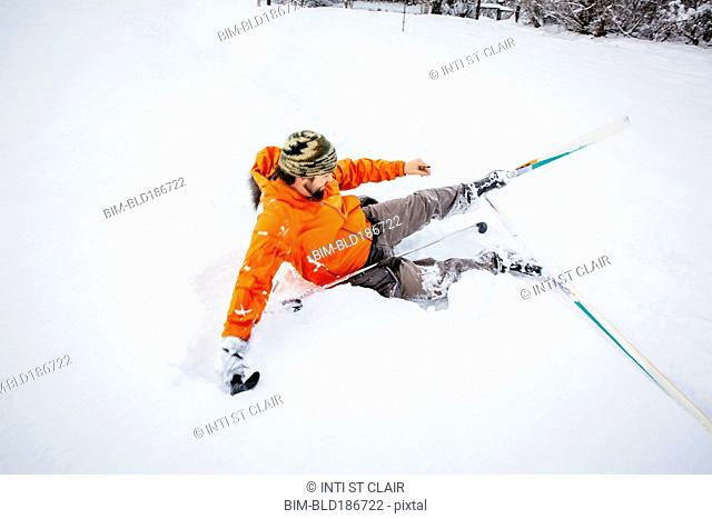 Caucasian man falling on cross-country skis in snow
