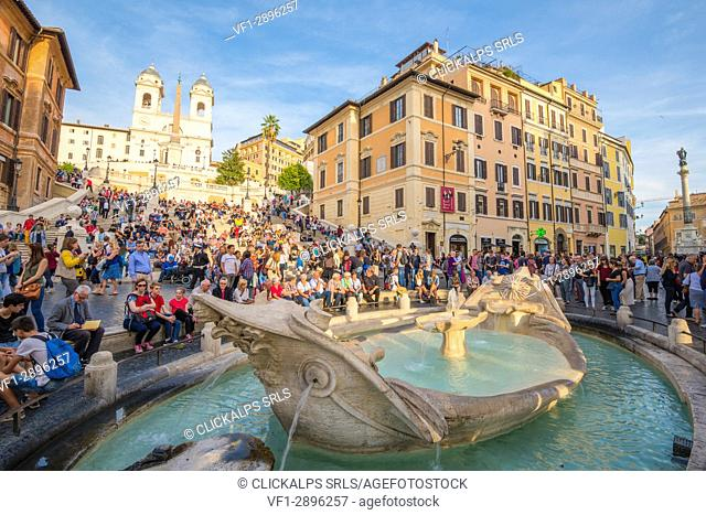 Rome, Lazio, Italy. People sitting on the Spanish Steps in front of Trinità dei Monti at sunset