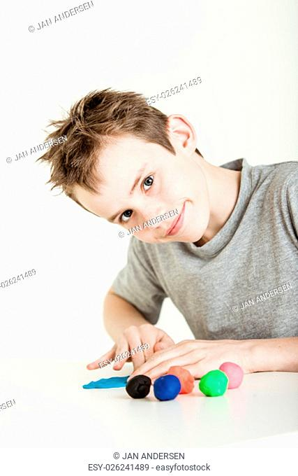 Adorable single male child in gray shirt rolling flat balls of clay in various colors on table