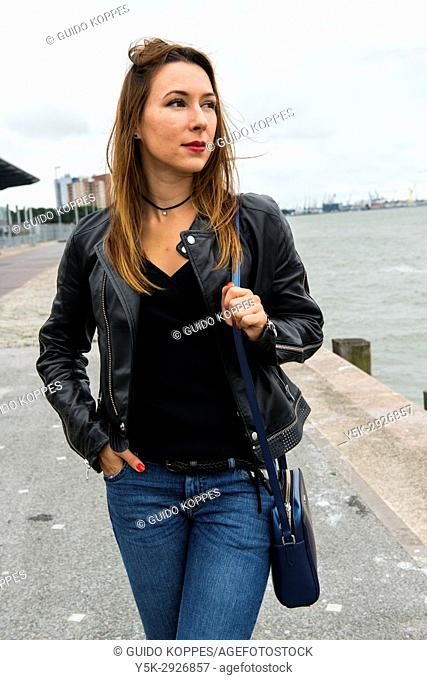 Rotterdam, Netherlands. Young adult brunette woman strolling the Port of Rotterdam Wilhelminapier