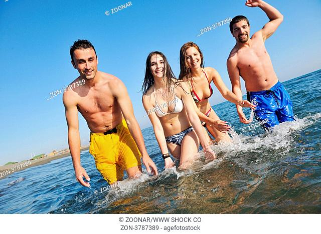 happy young people group have fun run and jump on beach beautiful sand beach