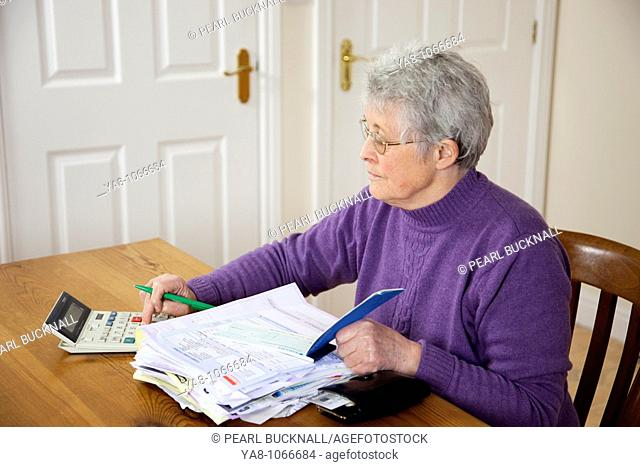 Britain, UK, Europe  Senior woman pensioner with a big pile of bills on the table using a calculator before writing a cheque