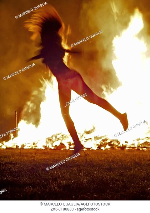 Teenager girl dancing in front of Bonfire of St. John's Night –nit de Sant Joan- celebrating Summer Solstice arrival. Olost village
