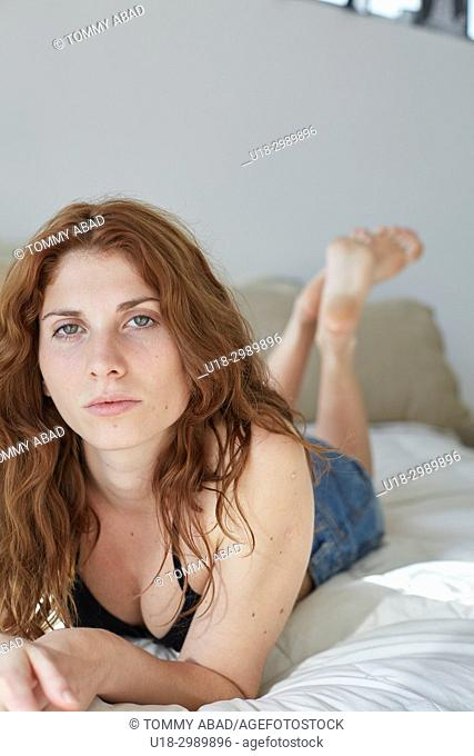 Young redhead woman lying down in bed, looking at camera