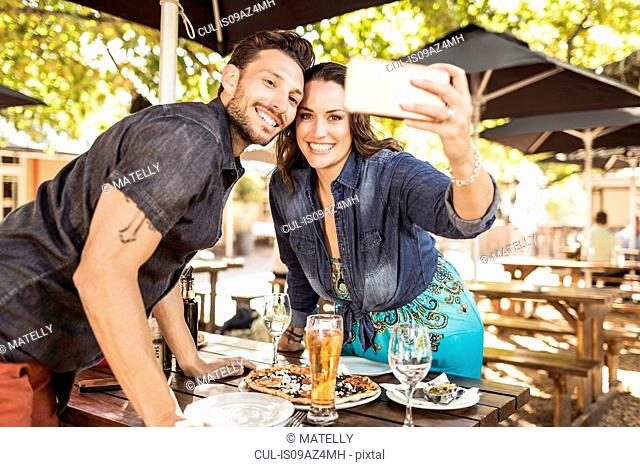 Couple at sidewalk cafe taking selfie