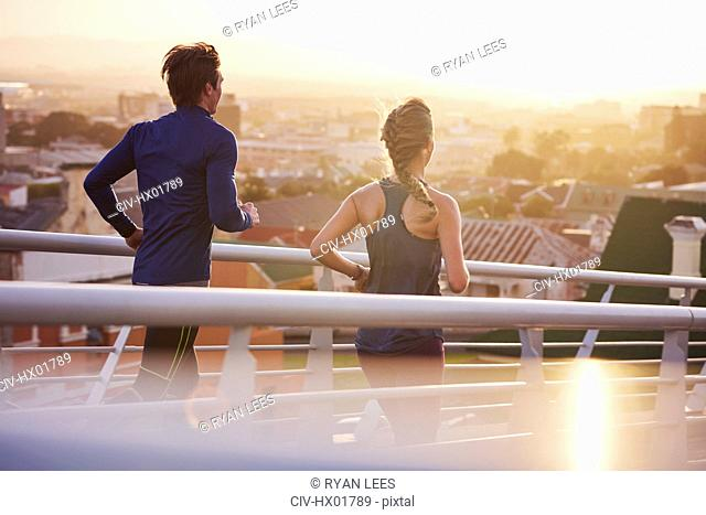 Runner couple running on footbridge with city view
