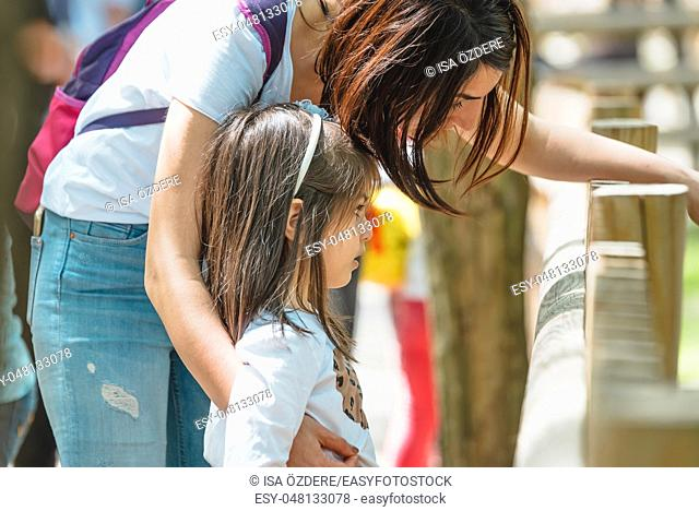 Young mom shows animal or something to her little daughter in zoo. Happy mother and daughter moments with love and natural emotion
