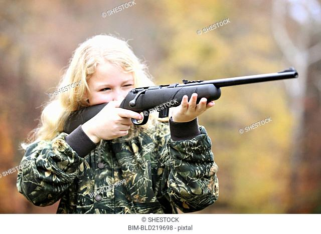 Girl in camouflage aiming rifle in forest