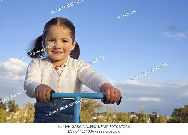 Smiling little girl playing with scooter. She is looking directly to camera