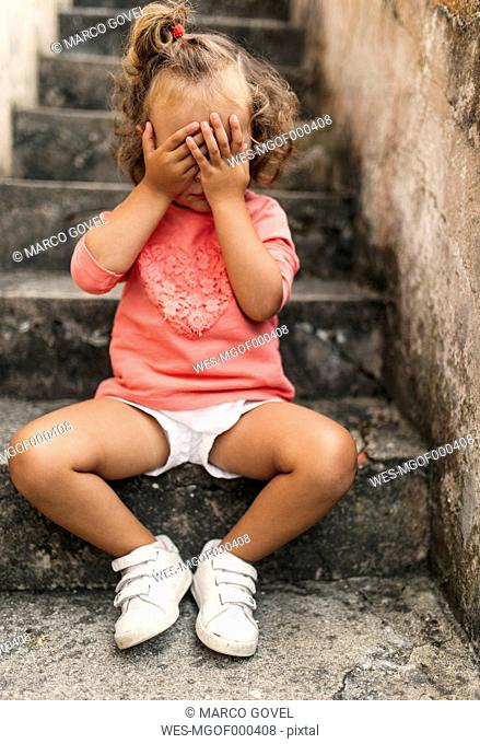 Little girl covering face with her hands