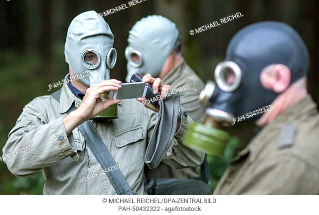 Visitors wear uniforms of the former National People's Army (NPA) of the German Democratic Republic (GDR) and gas masks during the reenactment of a military...
