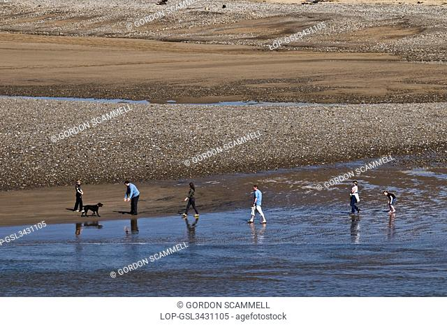 Wales, Vale of Glamorgan, Ogmore. A family walking along the beach at Ogmore