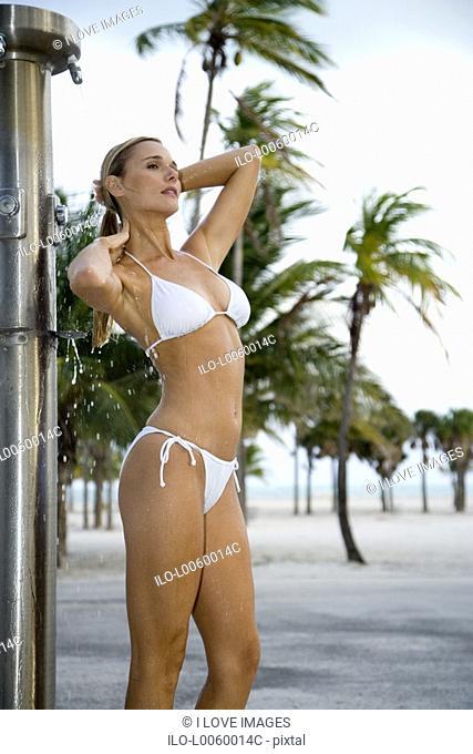 A woman in a bikini standing under an outdoor shower on a beach
