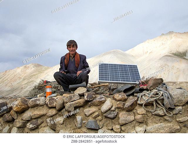 Wakhi nomad teenager sitting near a solar panel, Big pamir, Wakhan, Afghanistan