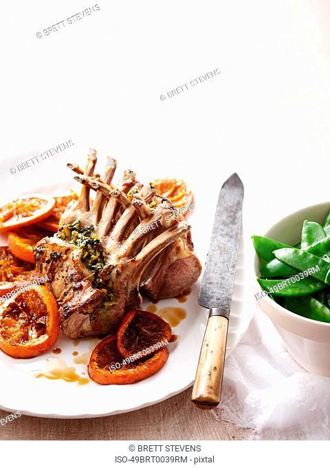 Roast lamb racks with orange and peas