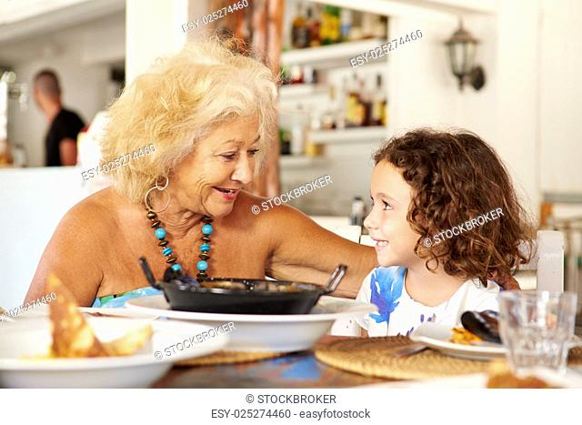Grandmother And Granddaughter Enjoying Meal In Restaurant