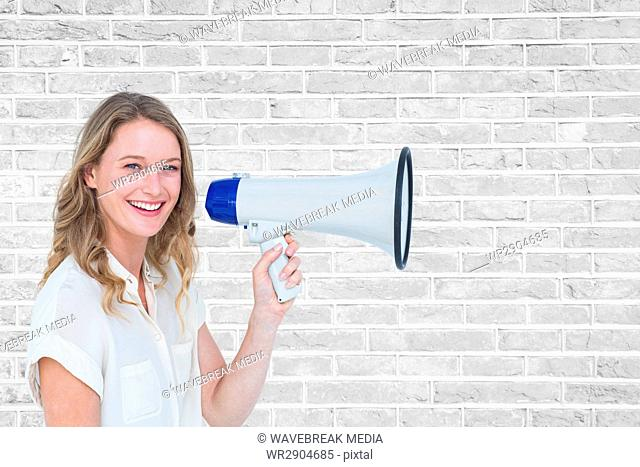 Portrait of smiling woman holding megaphone against brick wall