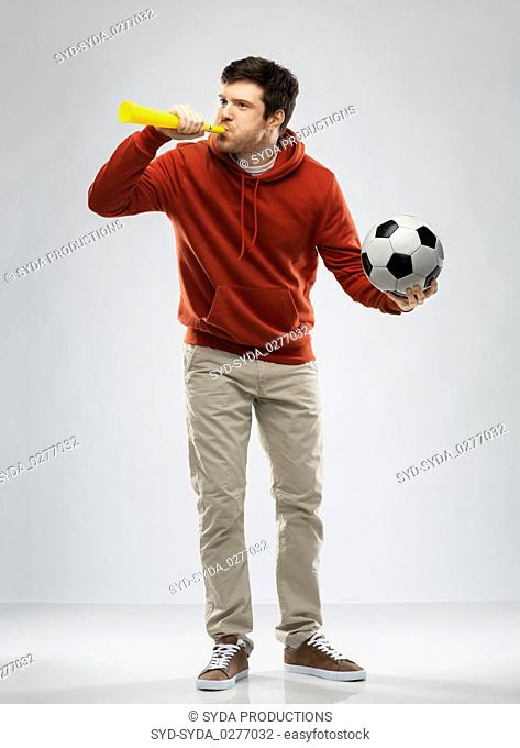 football fan with soccer ball blowing horn