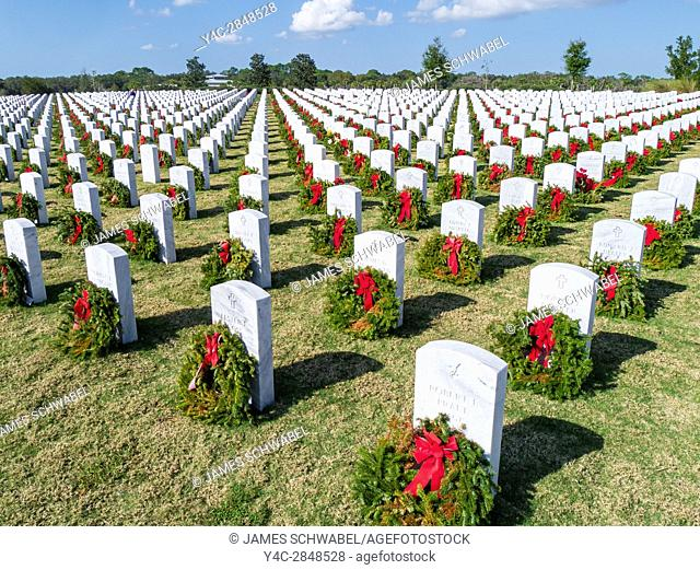 Rows of grave stones with wreaths & red bows in Sarasota National Cemetery in Sarasota Florida