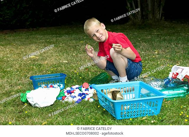 Young boy selecting waste