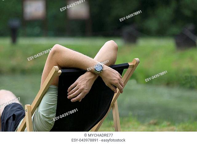 Young man lying on a deckchair in the garden, relax, day off