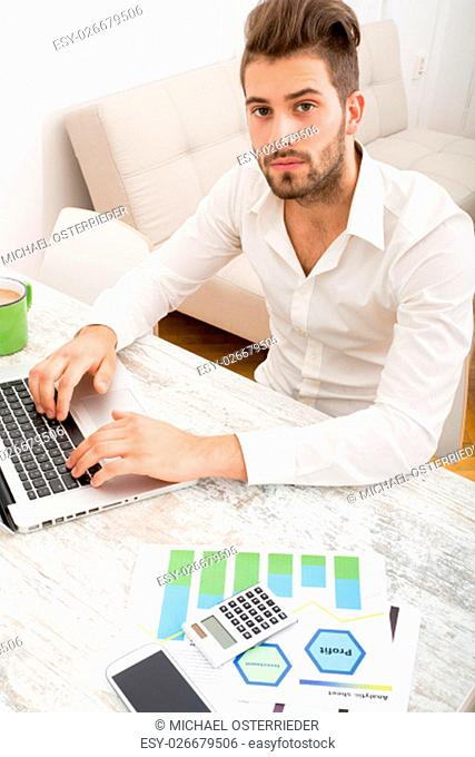 A young man checking his business statistics at home