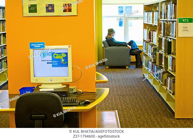 A man sitting in a modern library with a computer terminal and open shelves, Ontario, Canada