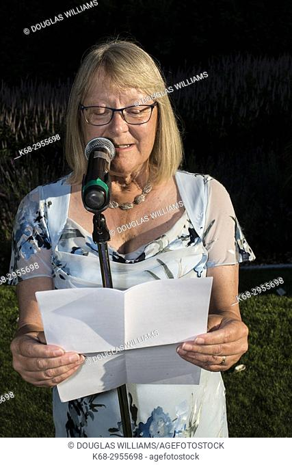 A woman, 63, reads a speech at outdoor wedding in West Vancouver, BC, Canada