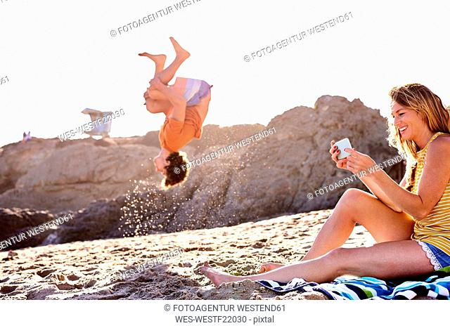 Young man on the beach doing a somersault with woman checking cell phone