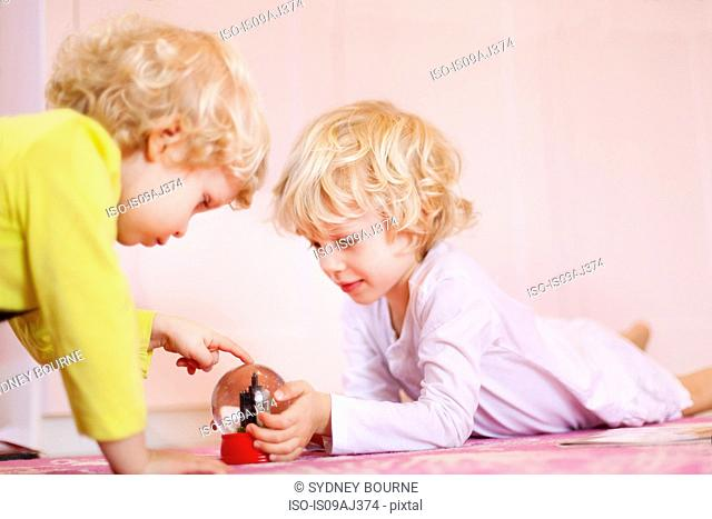 Two young brothers lying on rug gazing at snow globe