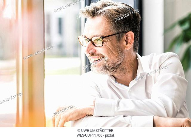 Smiling businessman with glasses looking sideways