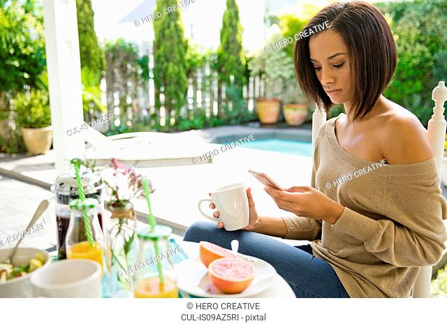 Young woman having breakfast looking at smartphone