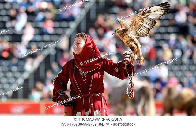 A falconer holding a bird of prey at the Hengstparade (lit. stallion parade)at the Haupt- und Landgestuet (lit. main and state stud farm)in Marbach, Germany
