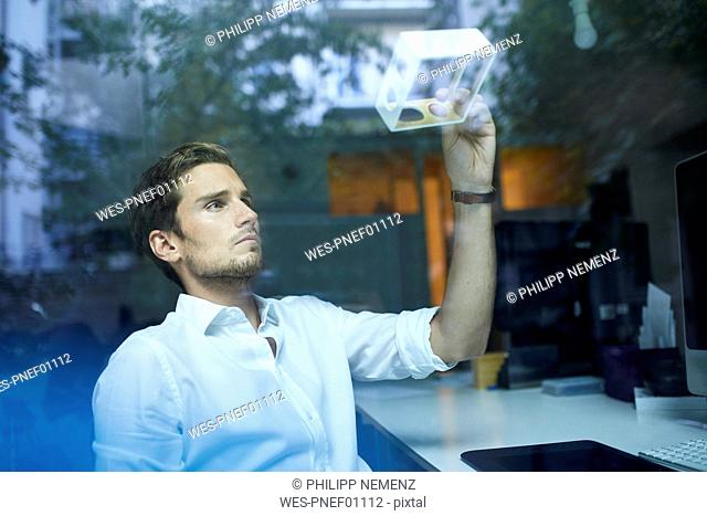 Portrait of serious young man behind windowpane examining prototype