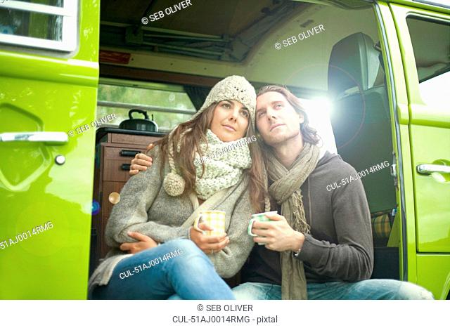 Couple drinking coffee in van