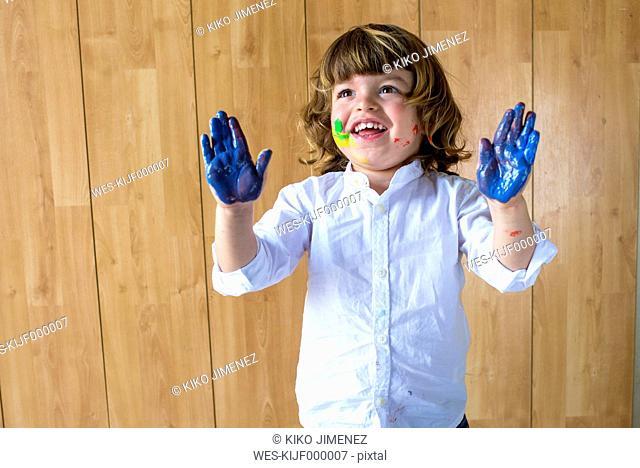 Portrait of smiling little boy showing his palms full of blue finger colour