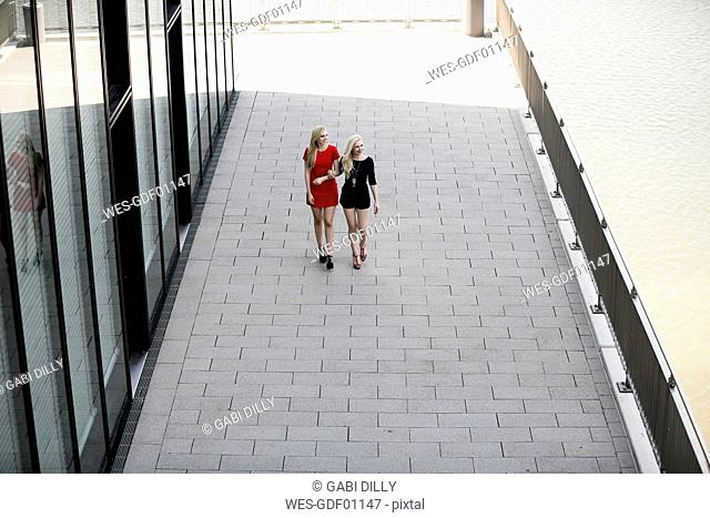 Two fashionable best friends walking arm in arm on a street
