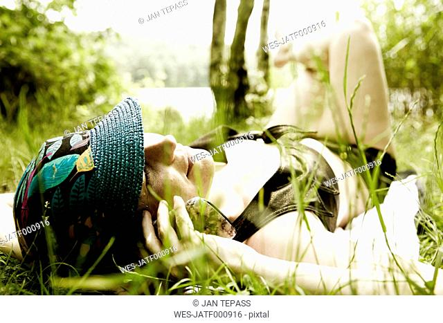 Woman lying on a meadow telephoning with cell phone