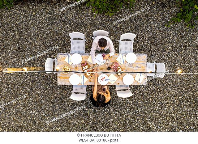 Italy, Tuscany, Siena, top view of young couple dining al fresco holding hands