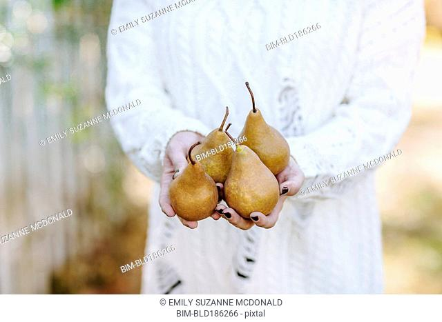 Caucasian woman holding pears