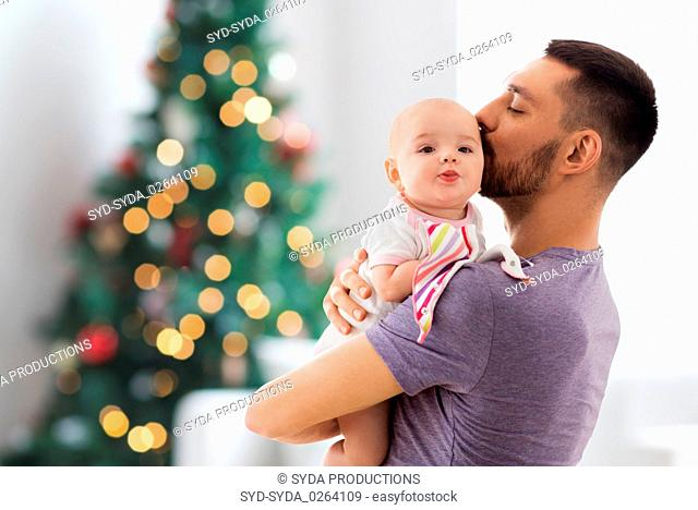 father kissing baby daughter over christmas tree