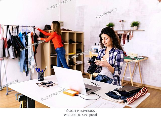 Fashion designer with camera and laptop in studio
