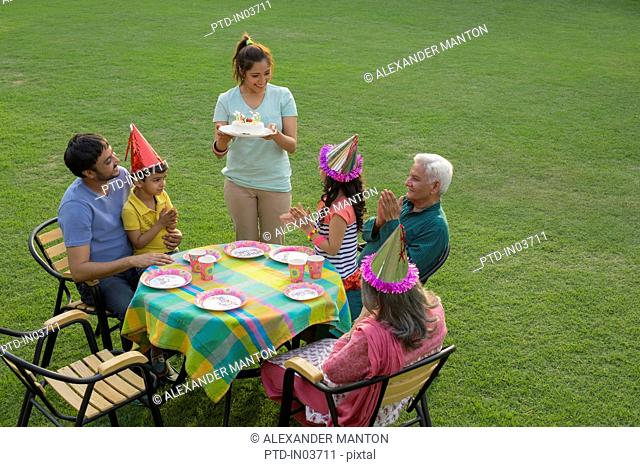 Mother holding birthday cake at party table with children (4-5), outside