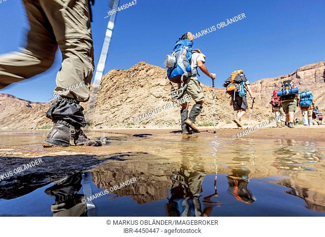 Hikers with backpacks crossing Fish River, Fish River Canyon, Namibia