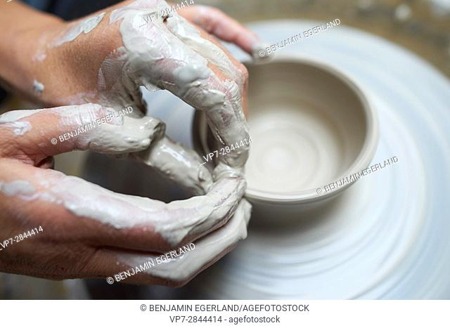 close-up of creative hands using clay to create pottery