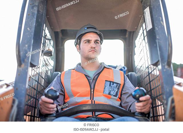 Young man driving excavator on construction site