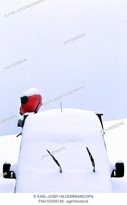 A canoe on the roof of a snow-covered camper represents a colorful speck in a snowy landscape on a parking lot close to Berghof, Germany, 27 January 2015